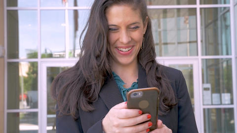 A beautiful happy businesswoman looking up and smiling from her smart phone app Footage