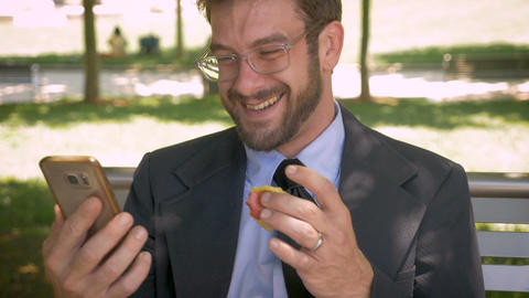 Attractive happy smiling businessman eating an organic apple and using his smart Footage