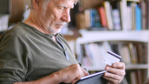 An attractive aging senior man ordering online with his credit card on his Live Action