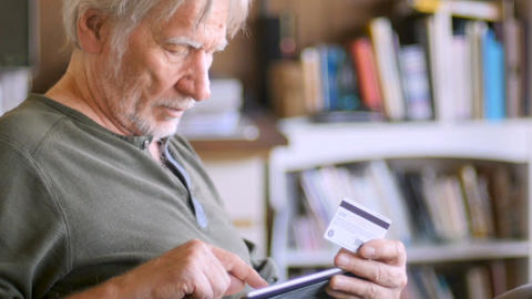 An attractive aging senior man ordering online with his… Stock Video Footage