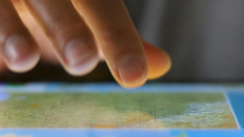 Extreme close up of finger selecting map on touchscreen digital tablet Footage