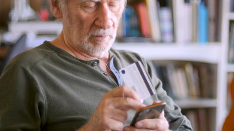 Handsome senior elderly retired man ordering on his mobile phone online with Footage