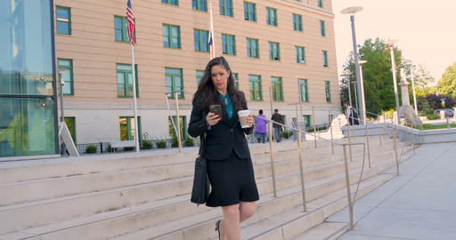 Hurried attractive businesswoman walking and multi tasking with smart phone down Footage