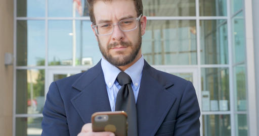 Portrait of handsome millennial man in a business jacket and tie on smart phone Footage
