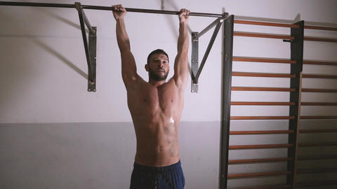 Youn man performing abdominal exercises on the horizontal bar at the gym Footage