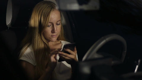 Woman surfing the net on phone in car at night Live Action