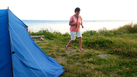 Woman is setting up a tent on the beach Footage