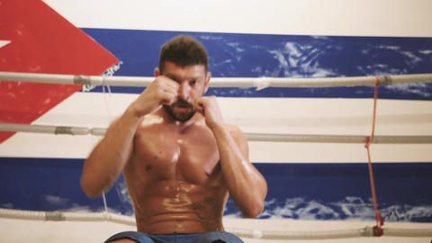 Muscular male boxer punching and doing abs workout Footage