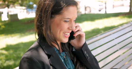 Successful happy businesswoman in her 30s talking on mobile phone on park bench Footage