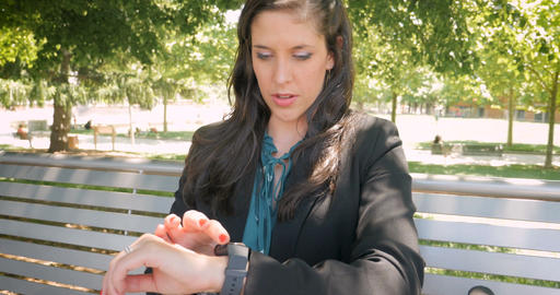 Pretty happy smiling businesswoman in her 30s using a smart watch outside on Footage