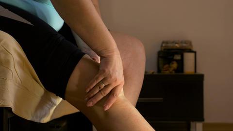 Adult woman sitting in bedroom rubbing her arthritic knee Footage