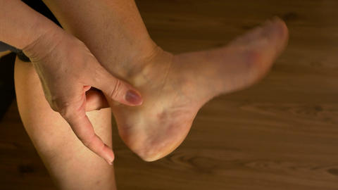 Closeup of woman massaging ankle and stretching foot suffering from pain Footage