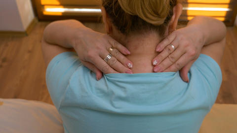 Adult house wife massaging back of neck and shoulder muscles relaxing at home Footage