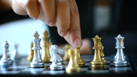 Dolly slider hands of business woman moving gold chess to kill silver knight che Footage