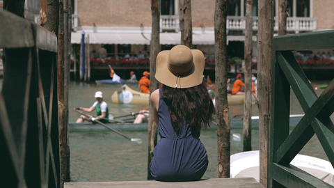 Woman with a hat sitting on a wooden pier with slow motion in Venice, Italy Filmmaterial