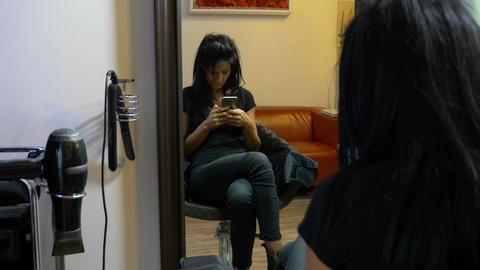 Young girl sitting on chair and texting on mobile phone at beauty salon Footage
