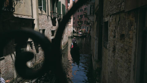 Water street with sailing gondolas view through the metal bridge fence in Venice Footage