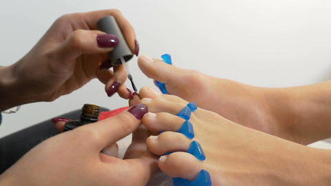 Beautician applies treatment on toe nails of client Footage