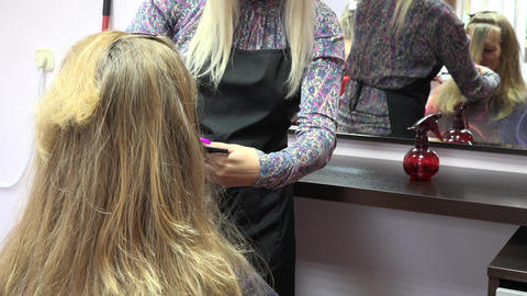 Hairdresser combing female customer hair in front of mirror. Focus change. 4K Footage