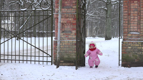 cute baby girl in overall walk through snowy retro park gate in winter. 4K Footage