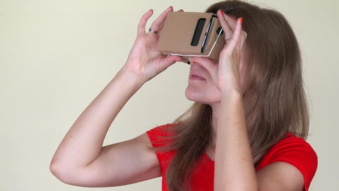 Serious woman using cardboard virtual glasses Footage