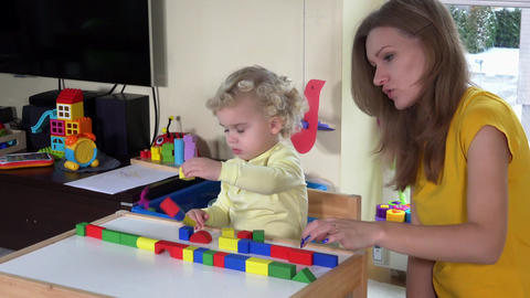 girl with mother playing colorful wooden bricks near small table at home Footage