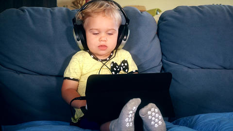 Little lovely child with big headphones watching cartoons on tablet computer Footage