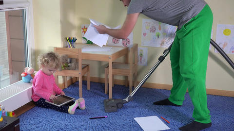 Man hoover child room and little girl play with tablet computer sitting on floor Footage