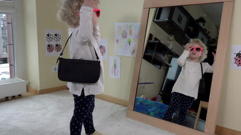 Mother give handbag and sunglasses for her daughter girl standing near mirror Footage