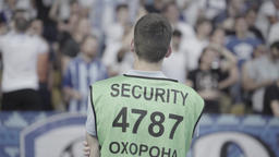 The steward guy watches the fans at the stadium. Security Live Action
