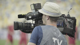 The cameraman takes news in the stadium. Reportage. TV. mass media Footage