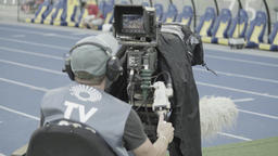 Tv cameraman with a camera at work in the stadium. Live. TV broadcast Footage