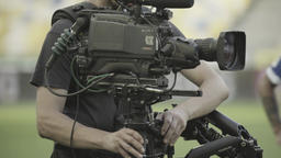 Steadicam cameraman with a camera while shooting a football team Footage
