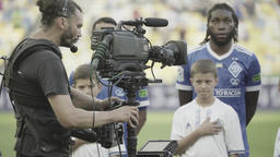 Cameraman with a camera and the Stedikam system while shooting a football team Footage