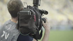Shooting news. Cameraman with a TV camera in the stadium Footage
