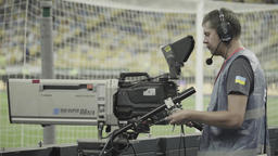 Cameraman with a camera in the stadium during a live TV broadcast Footage