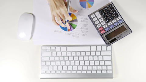 Woman accountant working with calculator and graph document on desk in office ライブ動画