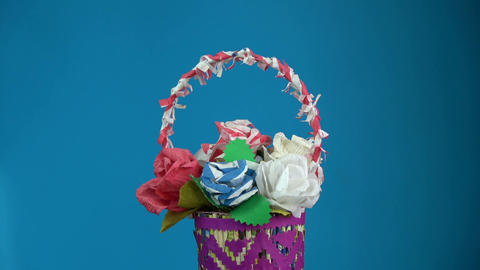 Rotating on blue background handmade paper basket with paper flowers Footage