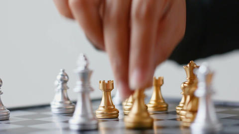 Close up shot hand of business woman moving golden chess to defeat a silver king Archivo