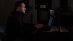 Man-the writer prints on the laptop at night ビデオ