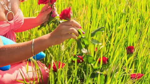Young Lady in Flower Garland Sits among Green Rice Field Footage