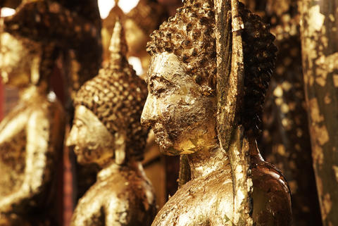 Antique Buddha Statues covered in gold leaf adornment フォト