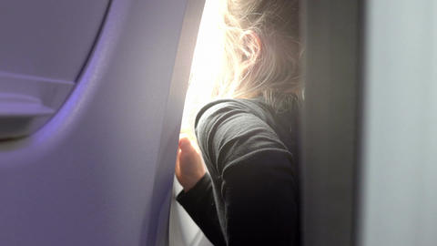 Video of child looking through the airplane window in real slow motion Image