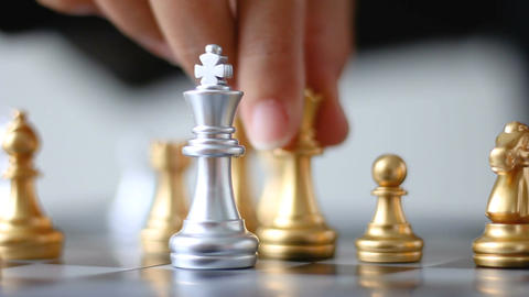 Close up shot hand of business woman moving gold king chess to kill silver king Footage