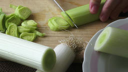 Fresh sliced leeks on a wooden board. Detail of leek slices Footage