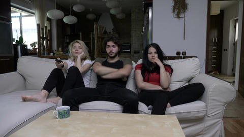 Two girls watch TV with their boy friend and switch the channels Footage