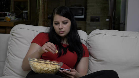 Sad woman sitting on the couch and eating popcorn Footage