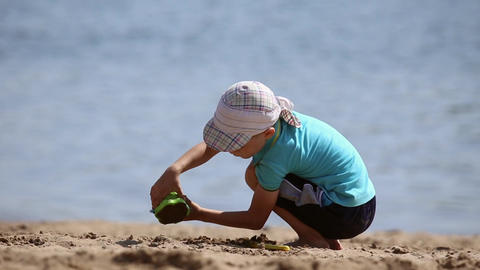 Little boy playing with sand on the beach Footage