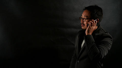 Businessman in Black Suit talking on cellphone on black wall background Image