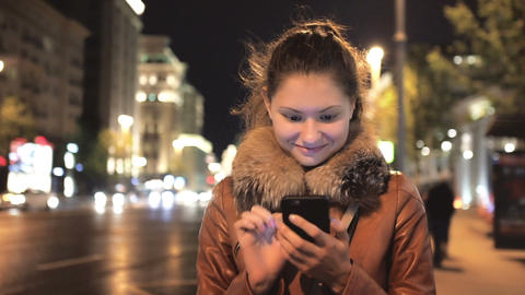 Happy Girl Using Smartphone against the Background of the Night City Archivo